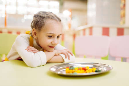 Little girl watching on sugar caramel in plate