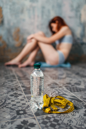 Water and measuring tape against anorexic woman