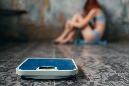 Anorexic woman sitting on the floor, weight loss