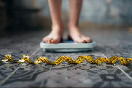 Female feet on the scales, measuring tape