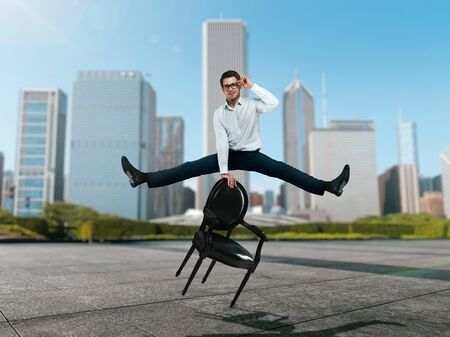 Businessman jump over chair against skyscrapers Stock Photo