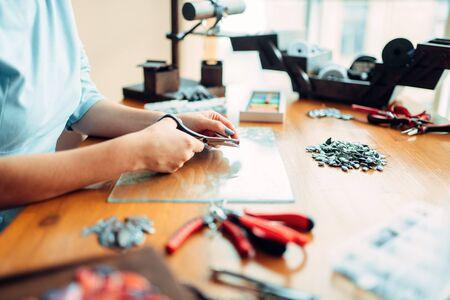 Female hands with scissors, top view, needlework