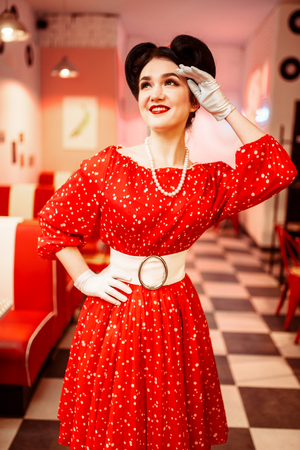 Pinup woman in retro cafe with checkerboard floor