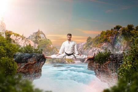 Martial arts master in kimonodo sitting on splits Stock Photo