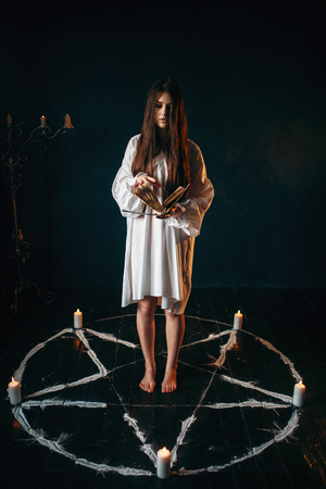 Woman standing in pentagram circle and reads spell