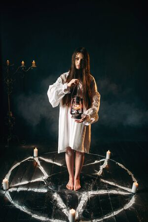Woman holds kerosene lamp, pentagram circle, magic Stock Photo
