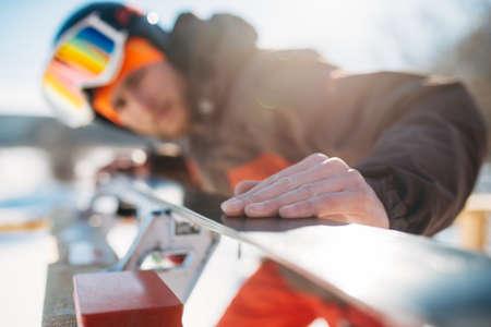Male skier checks skis before skiing, winter sport
