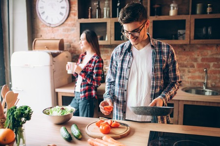 Husband hugs wife while she cooking fresh salad Standard-Bild