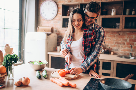 Couple hugs while cooking fresh vegetable salad