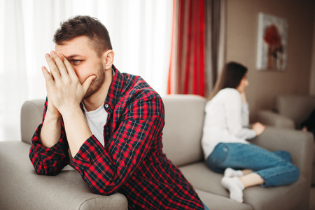 Couple sitting on couch, family conflict Stock Photo