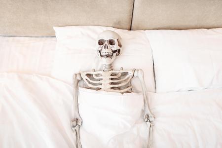 Funny human skeleton is lying in bad 版權商用圖片