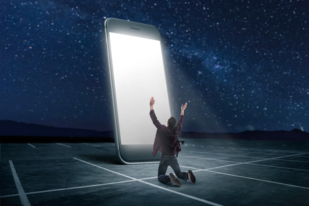 Phone addicted people concept. Man praying on his knees against large smartphone with glowing screen. Scaling effect