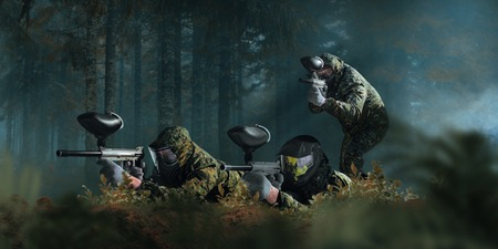 Paintball team shooting in forest battle