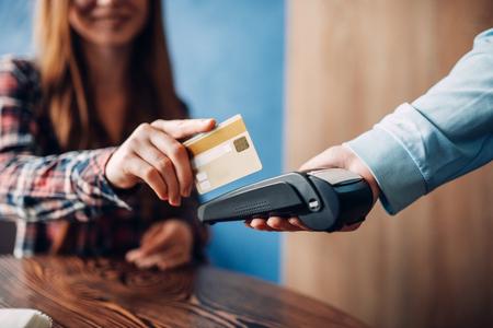 Junge Frau, die mit Kreditkarte im Café zahlt