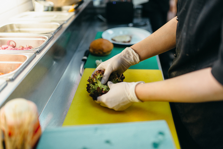 Male cook prepares fresh salad for burger Stock Photo