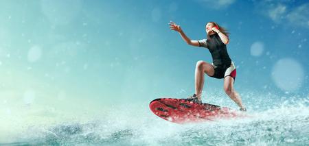 Female windsurfer in wetsuit riding on board Standard-Bild