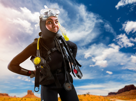Female diver in diving gear poses on the beach Stockfoto