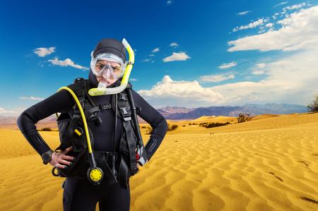 Diver standing in desert, underwater sport