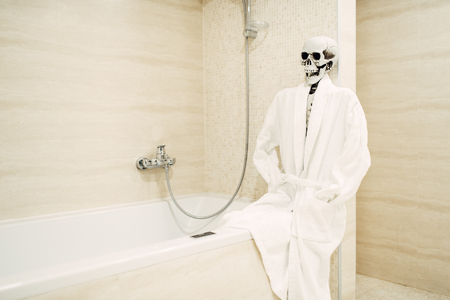 Human skeleton sitting on the edge of the bath 版權商用圖片