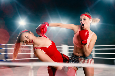Female kickboxers in action, fighting on the ring Archivio Fotografico