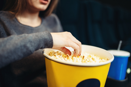 Woman eats popcorn while watching movie in cinema