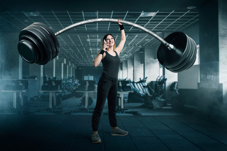 Female athlete with big barbell talking by phone
