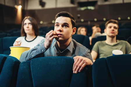 Scared man watching movie in cinema Stockfoto