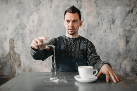 Autistic man pours water from the glass on table