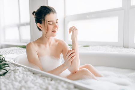 Sexy woman rubs the body with foam in the bath Stock Photo
