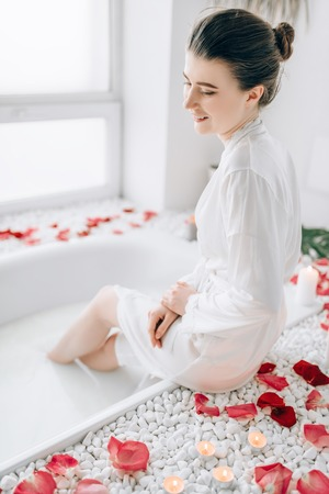 Woman sitting in bath decorated with rose petals