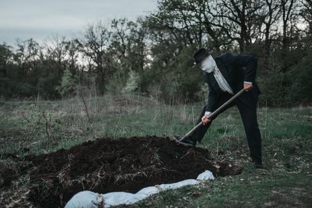 Der blutige Mörder gräbt ein Grab für das Opfer