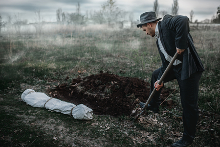 Killer is digging a grave for the victim in forest Stock Photo