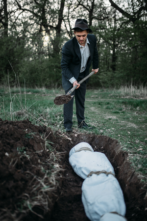Maniac with shovel buries victim into a grave Stock Photo
