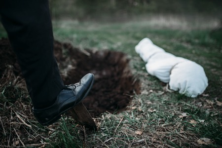 Male murderer with a shovel  is digging a grave Stock Photo