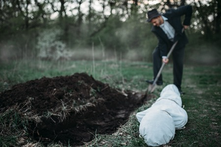 Killer is digging a grave for the victim in forest, the body wrapped in a canvas, serial maniac concept