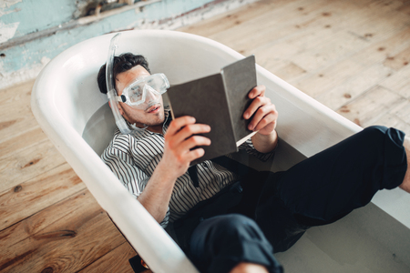 Businessman in flippers and mask lies in bathtub