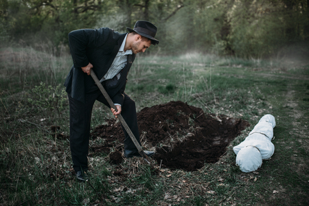 Male murderer with a shovel is digging a grave 스톡 콘텐츠