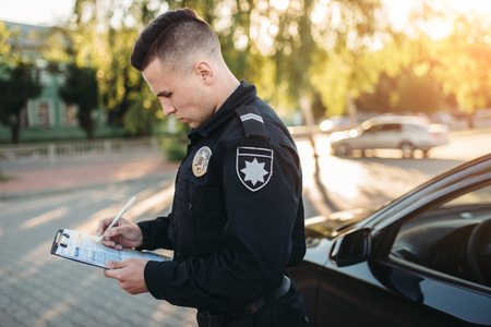 Male police officers writes a fine on the road Stock Photo