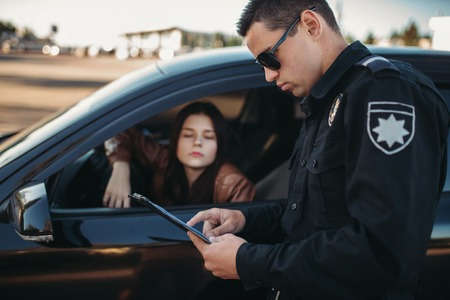 Cop in uniform checks license of female driver Stock Photo