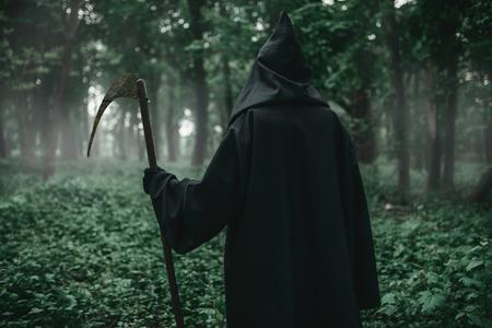 Tod mit einer Sense im dunklen Nebelwald
