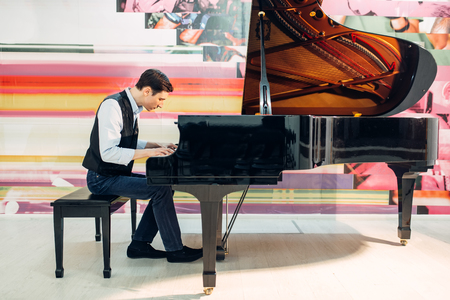 Male pianist practicing composition on grand piano Foto de archivo