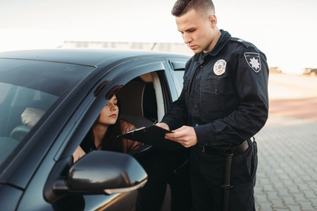 Cop in uniform checks license of female driver Archivio Fotografico