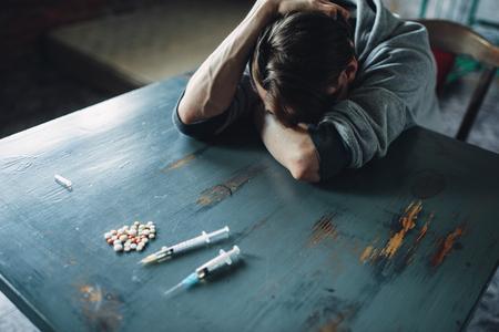 Hombre adicto a la mesa con drogas y jeringa