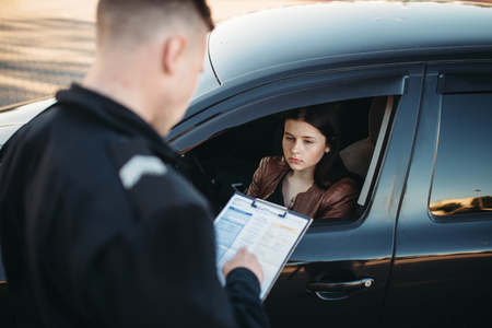 Policeman in uniform writes fine to female driver Imagens