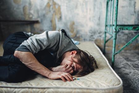 Hombre adicto a las drogas durmiendo en la cama después de la dosis