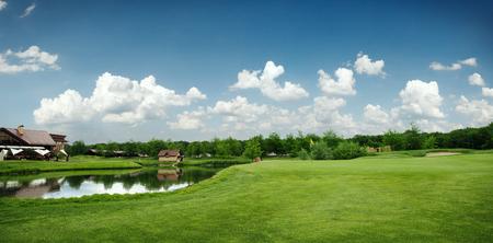Groen veld en meer om te golfen, golfbaan Stockfoto