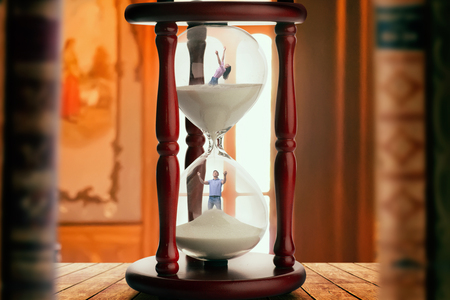 Man and woman inside hourglass, deadline concept Imagens