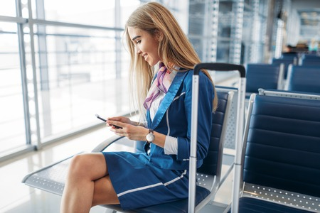 Stewardess using phone in waiting area in airport