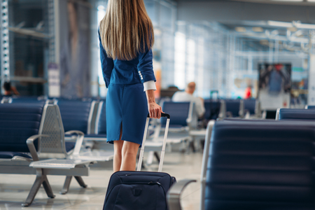 Air hostess going between seat rows in airport Stockfoto