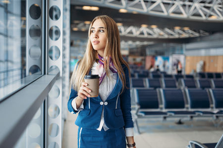 Stewardess with hand luggage and coffee in airport Stockfoto